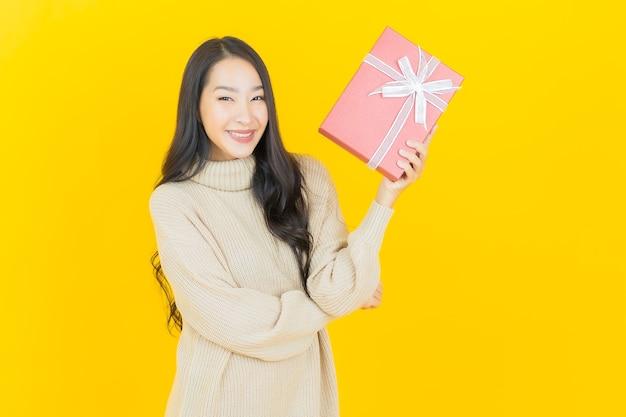 Улыбка женщины портрета красивая молодая азиатская с красной подарочной коробкой на желтой стене