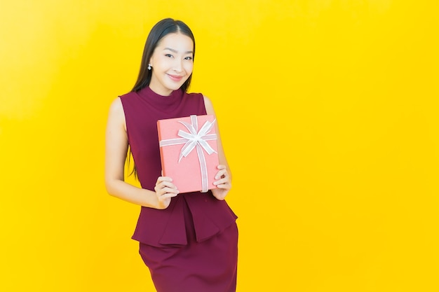 Portrait beautiful young asian woman smiles with red gift box on yellow wall