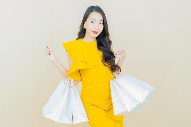 베이지색 벽에 쇼핑백을 들고 웃는 아름다운 젊은 아시아 여성