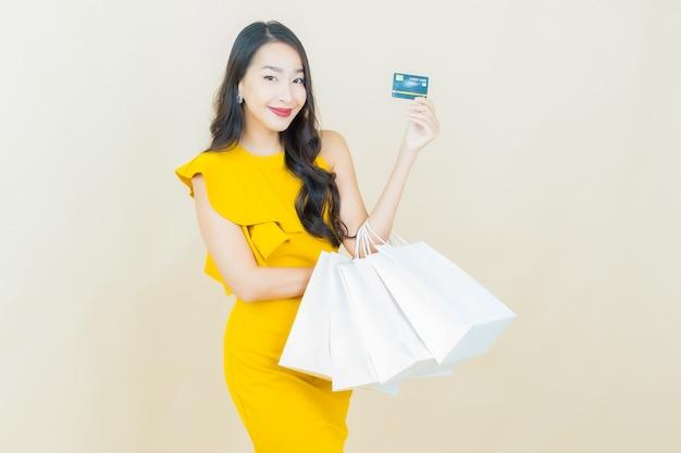 ベージュの壁に買い物袋で笑顔美しい若いアジアの女性の肖像画