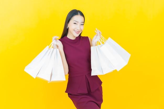 노란 벽에 쇼핑백을 들고 웃는 아름다운 젊은 아시아 여성