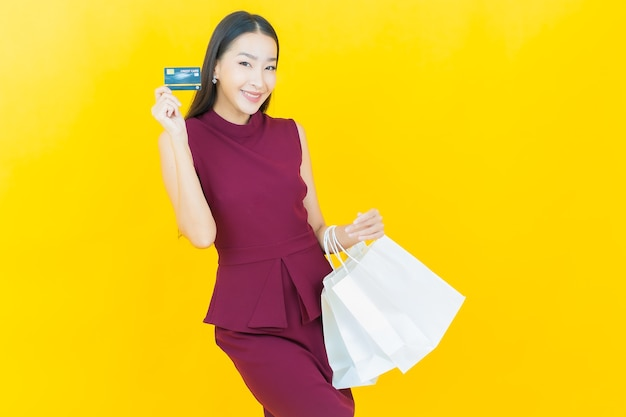Portrait beautiful young asian woman smiles with shopping bag on yellow wall