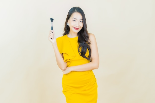 Portrait beautiful young asian woman smiles with smart mobile phone on beige wall