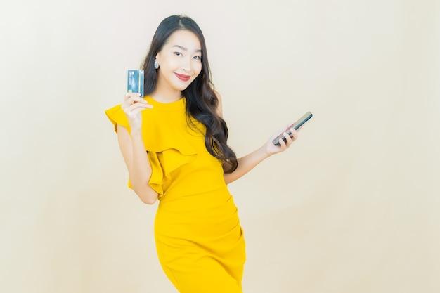 La bella giovane donna asiatica del ritratto sorride con il telefono cellulare astuto sulla parete beige