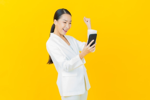 Portrait beautiful young asian woman smiles with smart mobile phone on color wall