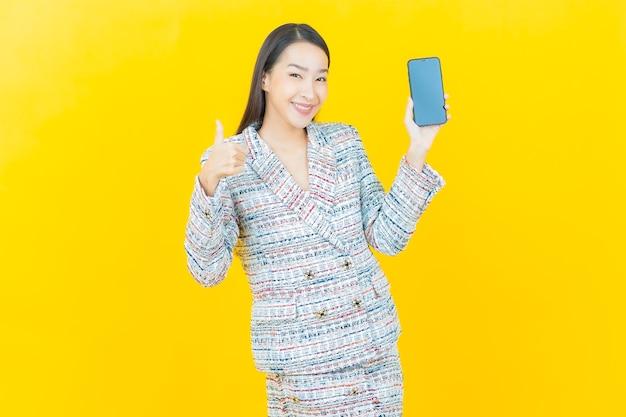 La bella giovane donna asiatica del ritratto sorride con il telefono cellulare astuto sulla parete di colore