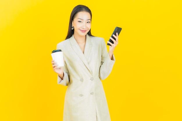 色の壁にスマートな携帯電話で笑顔のポートレート美しい若いアジア女性
