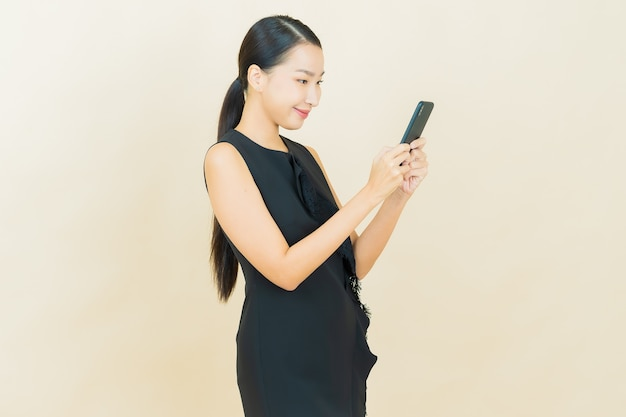 肖像画美しい若いアジアの女性が色の壁にスマート携帯電話で微笑む