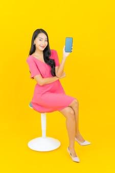 노란색 벽에 스마트 휴대 전화와 세로 아름 다운 젊은 아시아 여자 미소