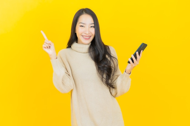 Portrait beautiful young asian woman smiles with smart mobile phone on yellow wall