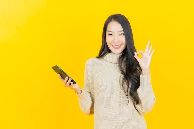 La bella giovane donna asiatica del ritratto sorride con il telefono cellulare astuto sulla parete gialla