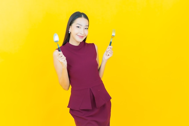 Улыбка женщины портрета красивая молодая азиатская с ложкой и вилкой на желтой стене