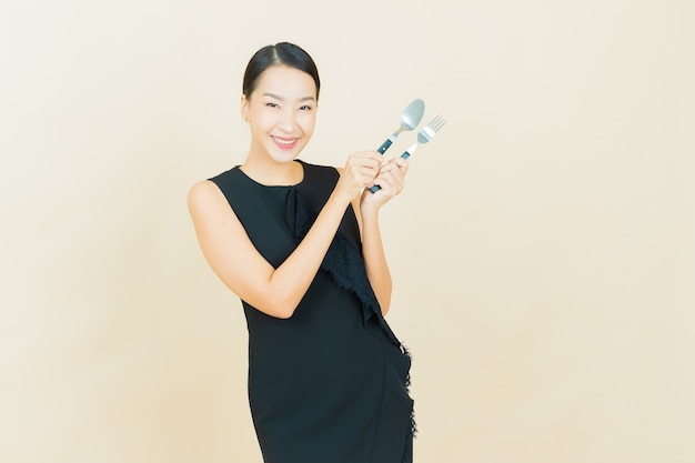 Portrait beautiful young asian woman smiles with spoon and fork on color wall