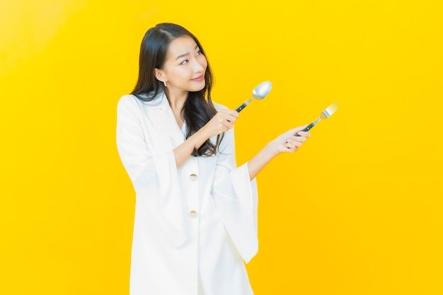 Portrait of beautiful young asian woman smiles with spoon and fork on yellow wall