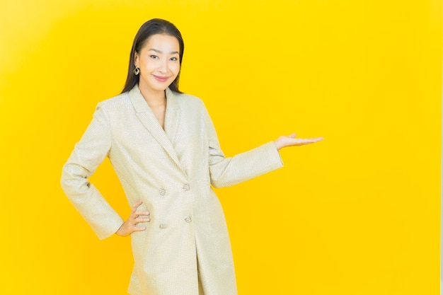 Portrait beautiful young asian woman smiles on yellow wall