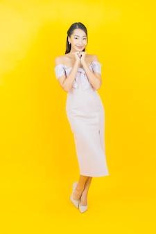 Женщина портрета красивая молодая азиатская усмехаясь и представляя на стене цвета