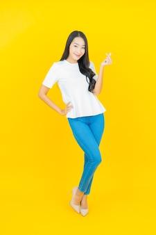 노란색에 웃는 초상화 아름 다운 젊은 아시아 여자