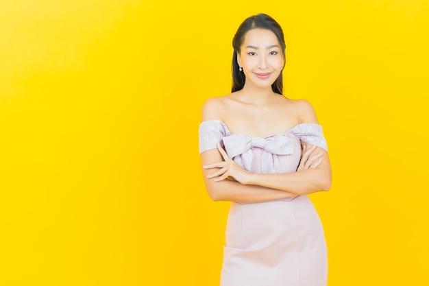 Bella giovane donna asiatica del ritratto che sorride e che posa sulla parete di colore