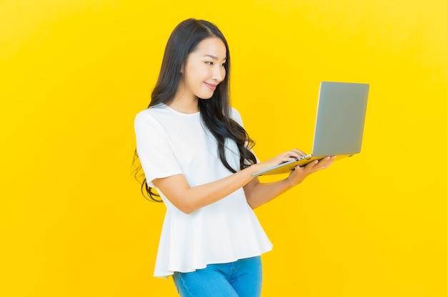 Женщина портрета красивая молодая азиатская усмехаясь с компьтер-книжкой компьютера на желтом