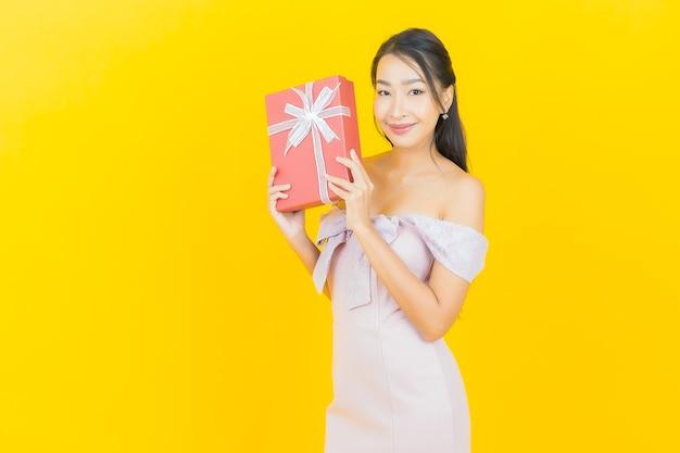 Женщина портрета красивая молодая азиатская усмехаясь с красной подарочной коробкой на стене цвета