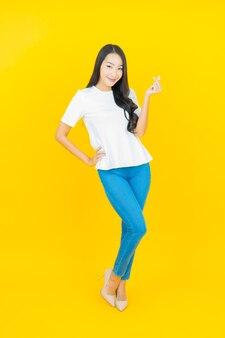 Ritratto bella giovane donna asiatica sorridente sul giallo