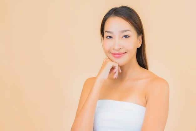Bella giovane donna asiatica del ritratto nella stazione termale con trucco naturale sul beige