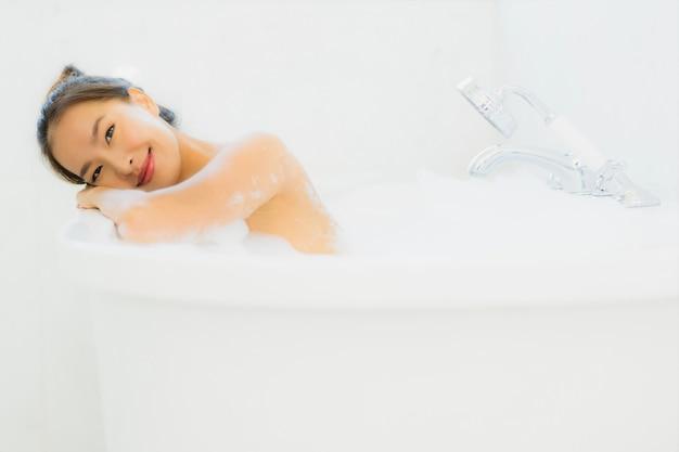 肖像画美しい若いアジア女性は浴室で浴槽を取る