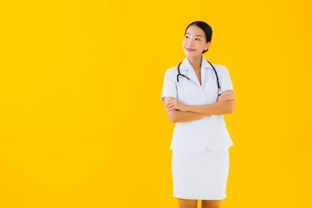 肖像画の美しい若いアジアの女性タイの看護師は患者の仕事の準備ができて幸せな笑顔を笑顔します。
