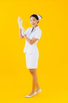 肖像画の美しい若いアジア女性タイの看護師は手袋を着用します。