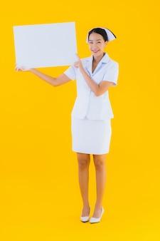 Медсестра красивой молодой азиатской женщины портрета тайская с пустой белой доской