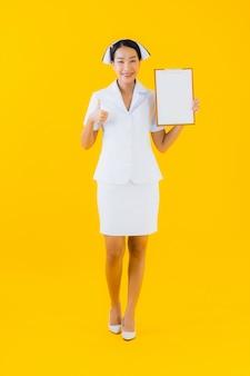 Infermiera tailandese della bella giovane donna asiatica del ritratto con la scheda bianca vuota