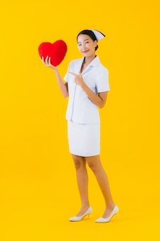 Portrait beautiful young asian woman thai nurse with heart pillow shape