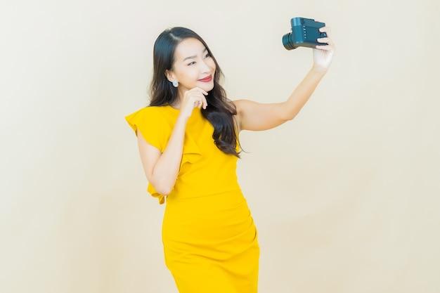 肖像画美しい若いアジアの女性はベージュの壁にカメラを使用します