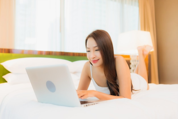 Portrait beautiful young asian woman use computer laptop on bed in bedroom interior
