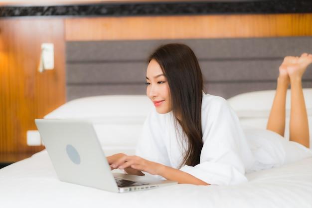 肖像画の美しい若いアジア女性は寝室のインテリアのベッドの上のコンピューターのラップトップを使用します。