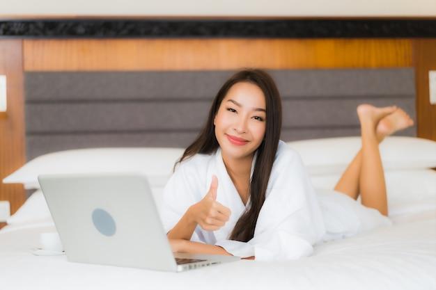 Компьтер-книжка компьютера пользы женщины портрета красивая молодая азиатская на кровати в интерьере спальни