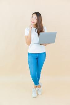 세로 아름 다운 젊은 아시아 여자 베이지 색에 컴퓨터 노트북을 사용