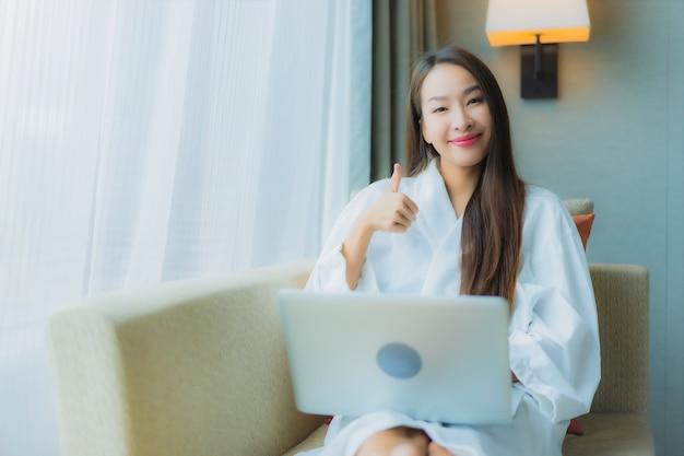 肖像画の美しい若いアジアの女性は、リビングルームエリアのソファーにコンピューターラップトップを使用します。