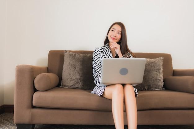 Компьтер-книжка компьютера пользы женщины портрета красивая молодая азиатская на софе в зоне интерьера живущей комнаты