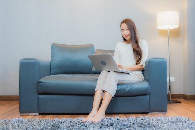 肖像画美しい若いアジアの女性は、リビングルームのインテリアのソファでコンピューターのラップトップを使用