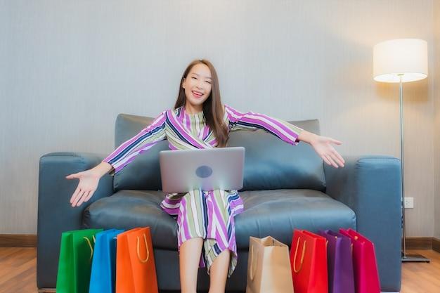 Компьтер-книжка компьютера пользы женщины портрета красивая молодая азиатская или мобильный умный телефон с кредитной карточкой для покупок онлайн
