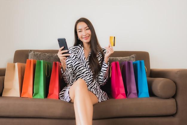 Компьтер-книжка компьютера пользы женщины портрета красивая молодая азиатская, умный мобильный телефон или наличные деньги для онлайн-покупок на софе в интерьере живущей комнаты