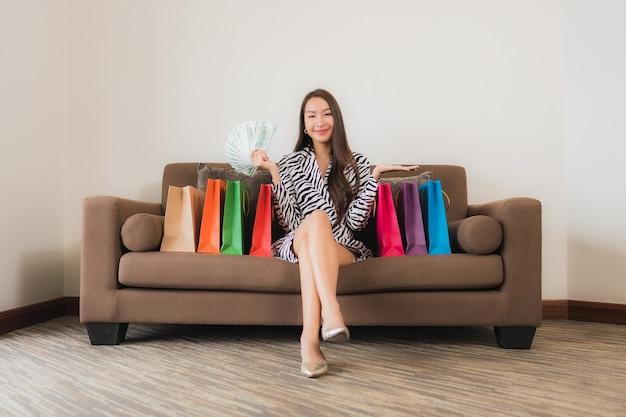 肖像画の美しい若いアジアの女性は、リビングルームのインテリアのソファーでオンラインショッピングのためのコンピューターのラップトップ、スマートな携帯電話または現金を使用します。
