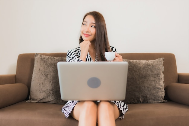 Portrait beautiful young asian woman use computer laptop on sofa in living room interior area