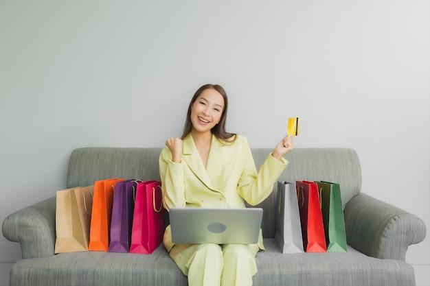 肖像画の美しい若いアジア女性は、リビングルームのインテリアのソファーでオンラインショッピングのためのクレジットカードでコンピューターのラップトップを使用します。