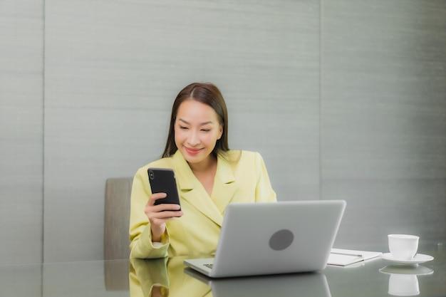 肖像画の美しい若いアジアの女性は、室内の作業テーブルにスマート携帯電話でコンピューターのラップトップを使用します。