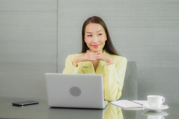 Computer portatile del computer di uso della bella giovane donna asiatica del ritratto con il telefono cellulare astuto sul tavolo di lavoro alla stanza interna