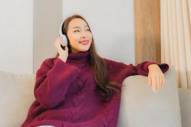 肖像画の美しい若いアジアの女性は、リビングルームのインテリアのソファーで音楽を聴くためのヘッドフォンを使用します。