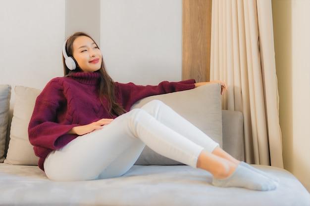 La bella giovane donna asiatica del ritratto usa le cuffie per ascoltare musica sul divano nell'interno del soggiorno