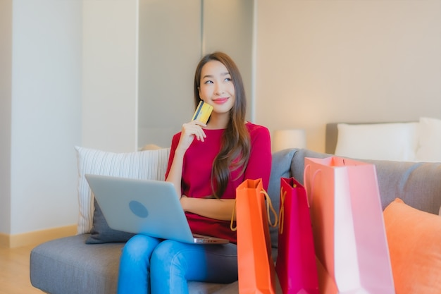 Portrait beautiful young asian woman use laptop computer with credit card